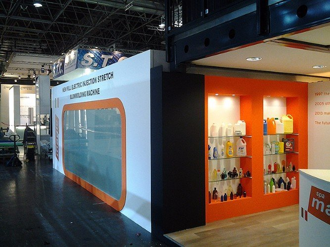 uno stand di color bianco e arancione con delle mensole e delle confezioni di prodotti esposti