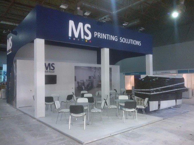 uno stand di MS printing Solutions e davanti dei tavoli e delle sedie bianche e nere