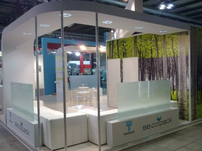 uno stand di Trioplast con due divani e un tavolo con delle sedie in plexiglass