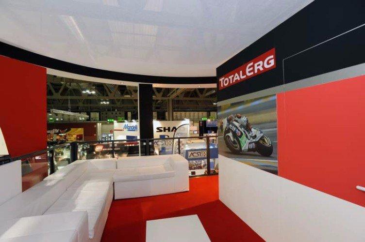uno stand di Total Erg con divani bianchi e pareti rosse