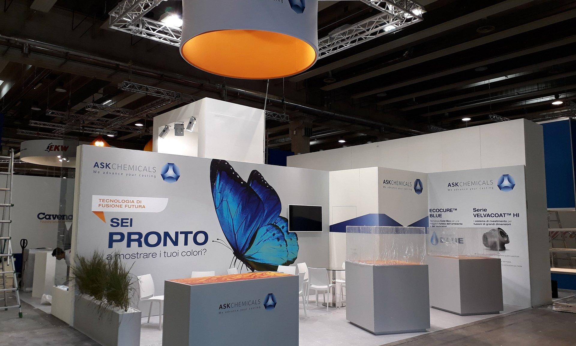 uno stand tre banconi e dei muretti con le scritte blu e un disegno di una farfalla