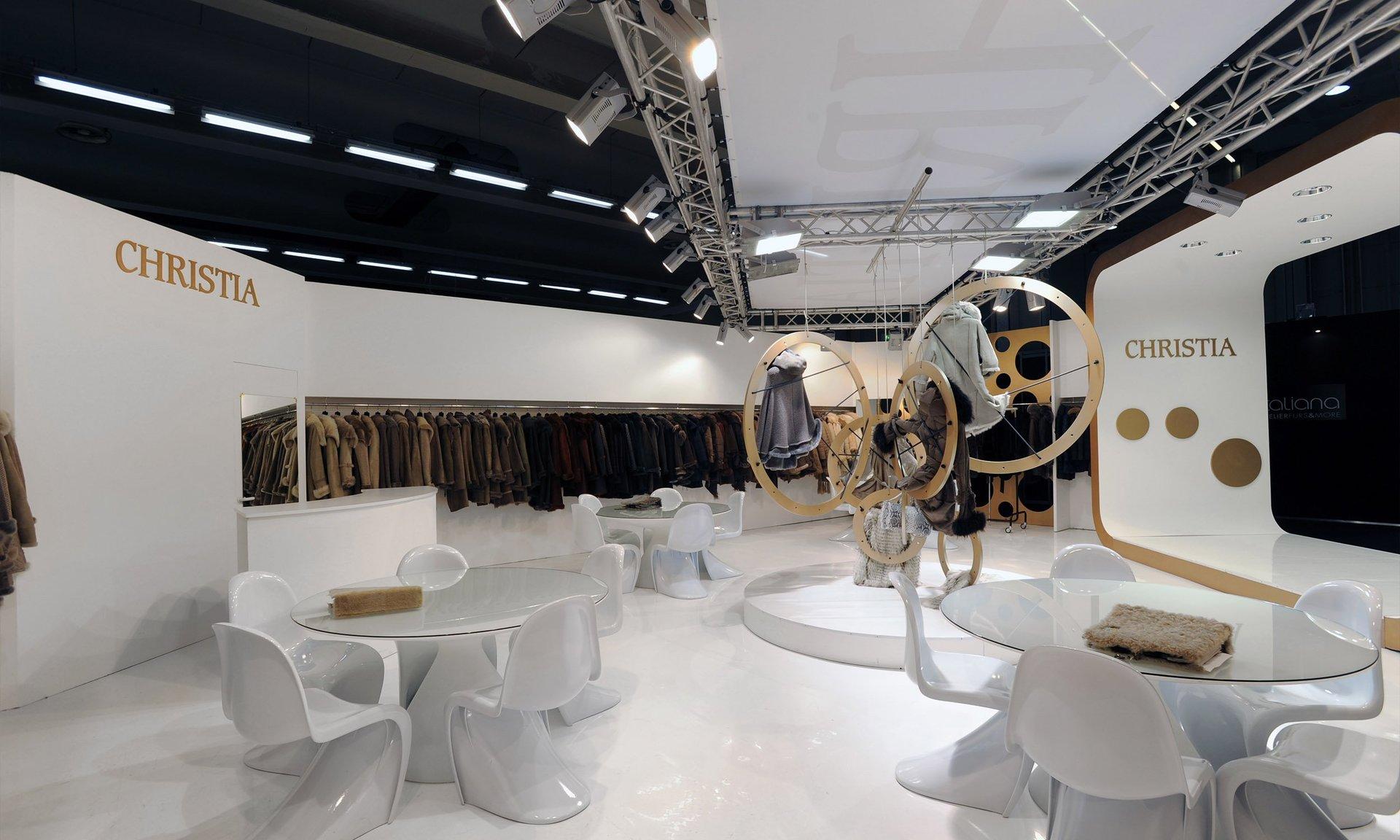 dei tavoli in plexiglass, delle sedie bianche in uno stand della boutique Christia