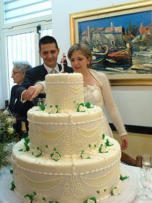 due sposi mentre tagliano una torta nuziale