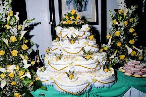 una torta nuziale decorata con delle rose gialle e delle foglie verdi