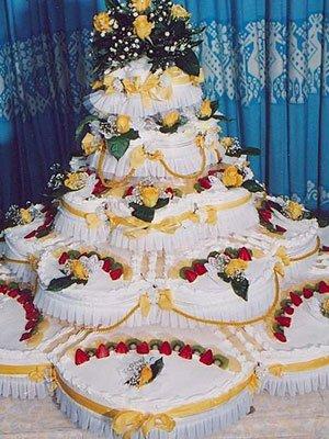 una torta nuziale decorata con dei nastri gialli, foglie verdi e delle fragole