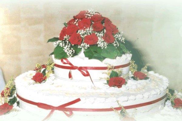 una torta a due piani e decorazione con delle rose e dei nastri di color rosso