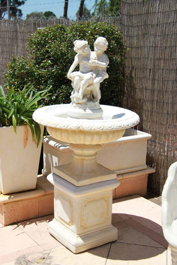 stone birdbath with a statue of children on top