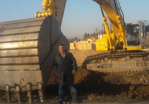 Uomo accanto la pala della scavatrice