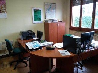 uno studio con monitor e una scrivania curva in legno