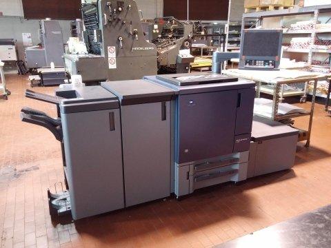 una macchina da stampa e accanto un monitor