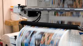 una macchina da stampa e sotto un rotolo di stampe a colori