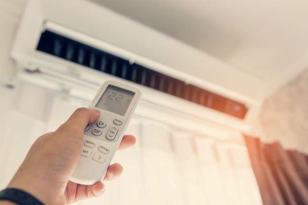 una persona usando il telecomando di un condizionatore