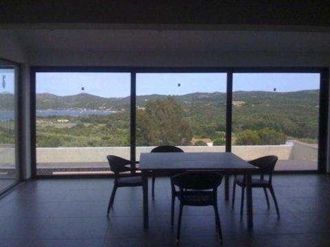 un tavolo con delle sedie in una stanza circondata da vetrate