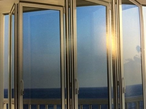 delle finestre in pvc viste da vicino e dietro una ringhiera con vista del mare