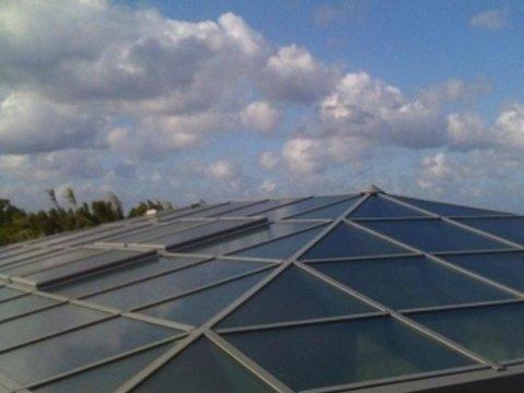 un insieme di vetrate che compongono un tetto e dietro vista del cielo azzurro e delle nuvole