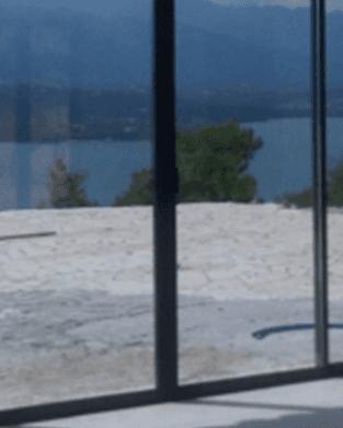 una porta finestra e dietro vista del patio in pietra con un albero e il mare