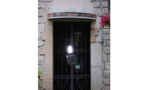 una serranda anti intrusione in una casa con i muri di ingresso in pietra