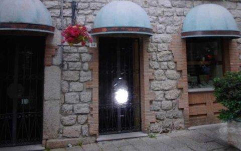 uno stabile con facciata in pietra con tre serrande anti intrusione e sopra delle tettoie