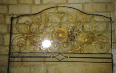 una testata di un letto in ferro battuto color nero e dorato