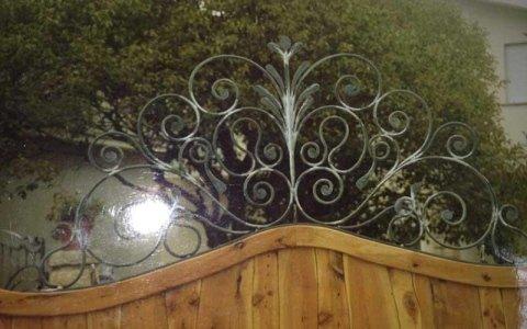un cancello in legno con sopra delle finiture in ferro battuto a forma di spirale