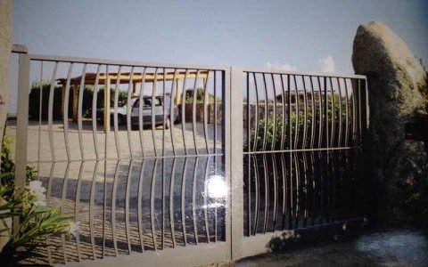 un cancello in ferro battuto color grigio e in fondo una macchina parcheggiata sotto una tettoia in legno a 4 travi
