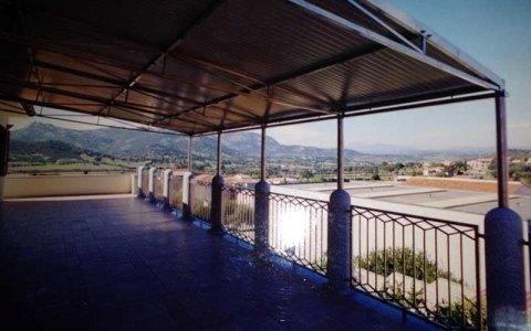 vista di una tettoia in ferro all'esterno di uno stabile e sotto un terrazzo con ringhiere in ferro battuto