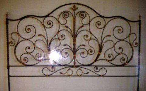 una testata di un letto in ferro battuto a piccole spirali