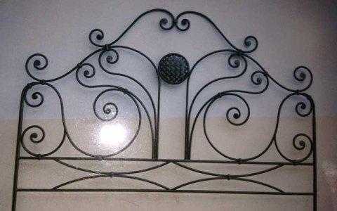 una testata di un letto in ferro battuto color nero