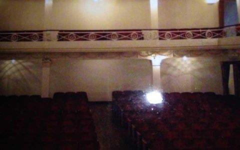 interno di un cinema con delle poltroncine bordeaux e sopra una balconata con delle ringhieri color panna in ferro battuto