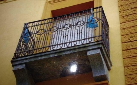 vista dal basso verso l'alto di un balcone con ringhiera in ferro battuto
