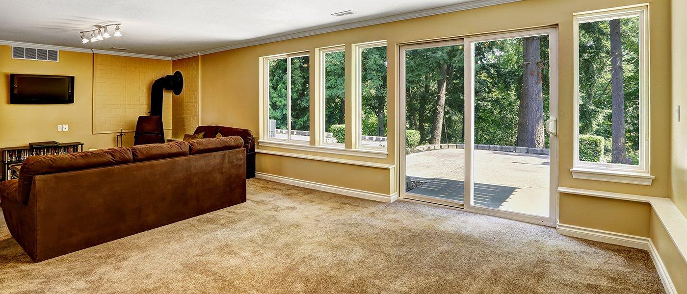 un salotto con sulla sinistra un divano marrone, una tv a muro e dei serramenti in pvc bianco