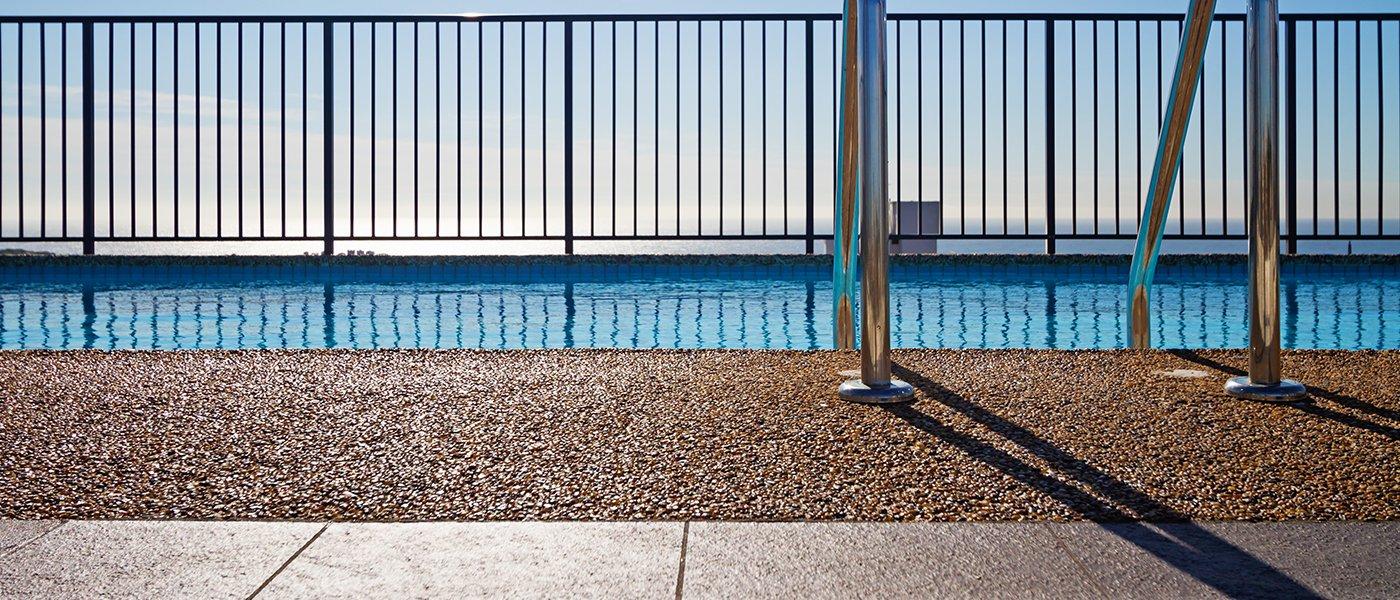 un terrazzo con una pavimentazione azzurra lucida, una moquette marrone e in fondo un parapetto in ferro