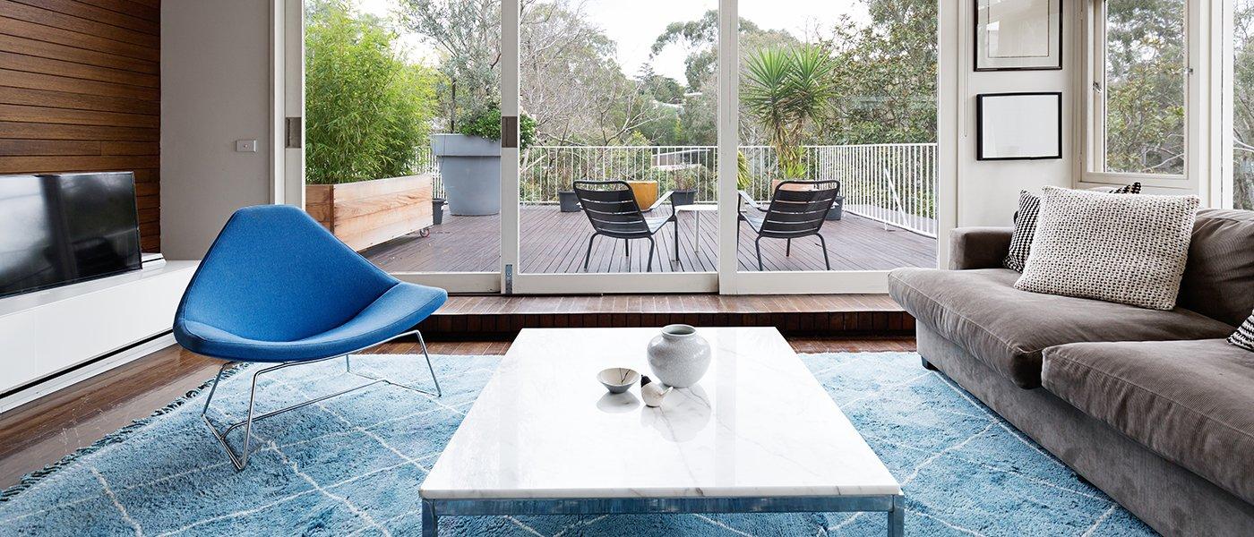 un salotto con sulla sinistra una poltrona azzurra un tavolino al centro, un divano sulla destra e una porta finestra di color bianco con  vista di due sdraio sul terrazzo