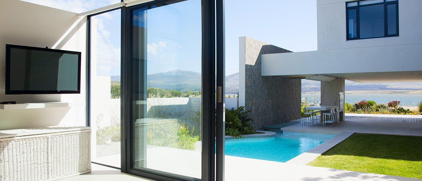 delle porte finestre in vetro scorrevoli, sulla sinistra una tv a muro e fuori vista di una piscina in un giardino