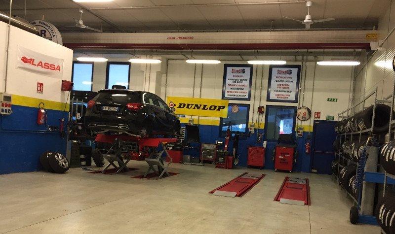interno dell'officina con sulla sinistra una vettura Opel di color nero metallizzato sul ponte elevatore e sulla destra diversi pneumatici negli scaffali di ferro