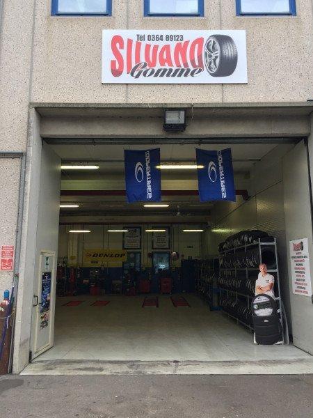 entrata  dell'officina vista dall'esterno con in alto l'insegna Silvano Gomme, due bandiere blu che pendono dall'alto e un uomo con delle gomme su un rilievo di cartone
