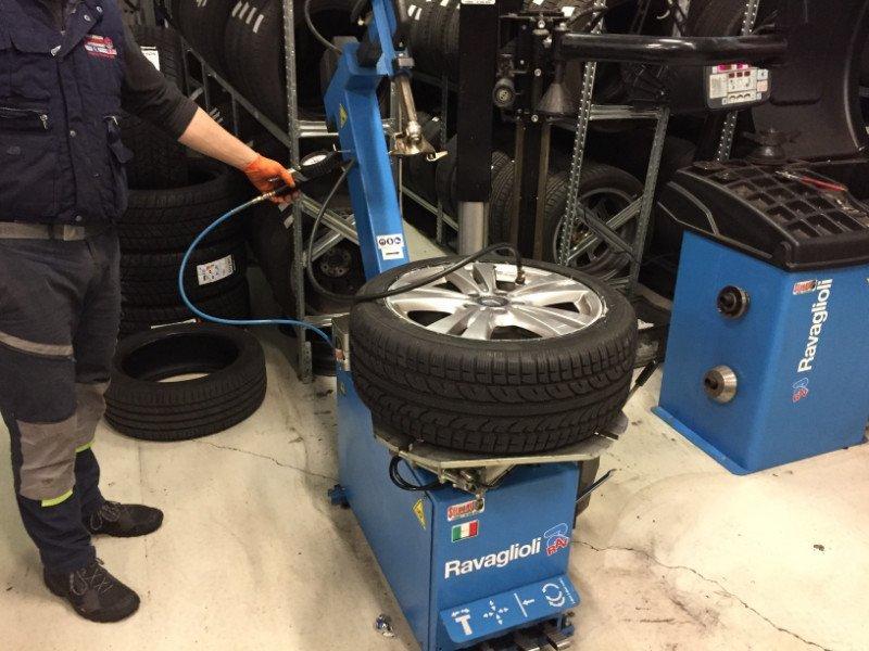 un gommista misura la pressione di un pneumatico appoggiato su una struttura in ferro di color blu