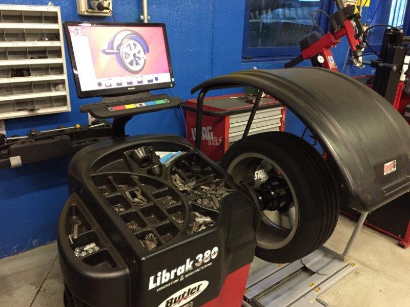 vista di un macchinario per l'equilibratura con un monitor e accanto un pneumatico