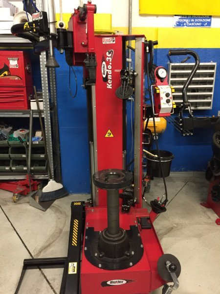 vista di un macchinario rosso che serve per inserire la gomma nel cerchione