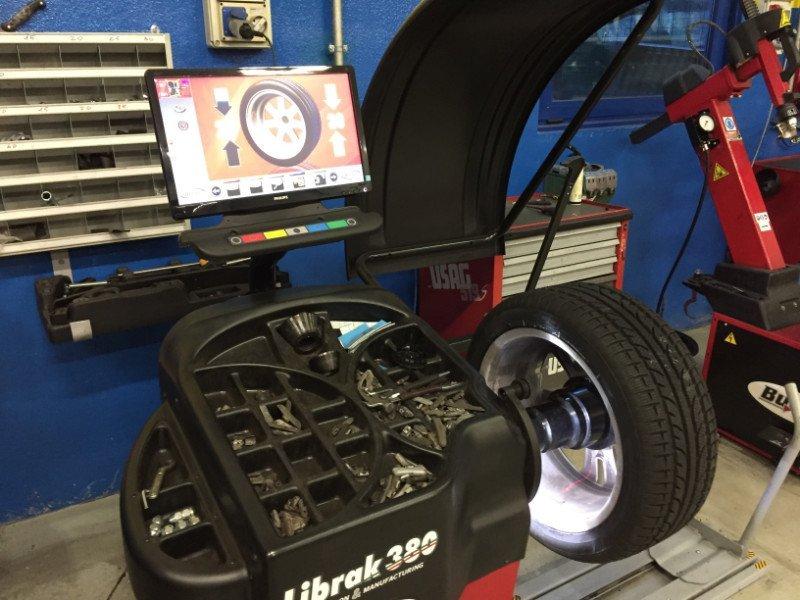 vista del macchinario per l'equilibratura con il monitor e accanto una ruota