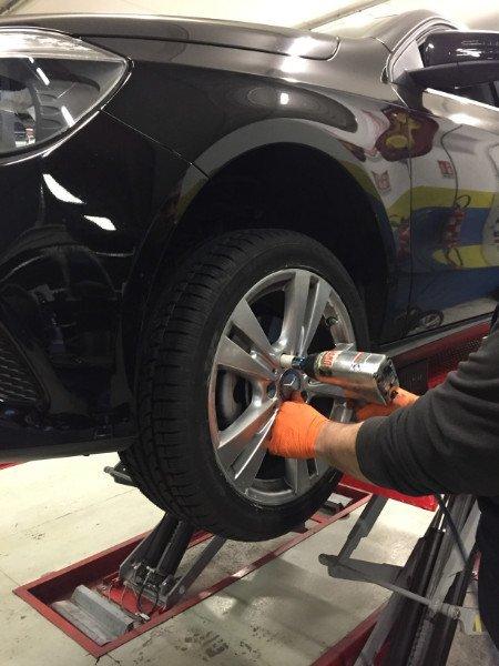 un gommista sta svitando con il trapano un bullone di una ruota di una vettura di color nero metallizzato