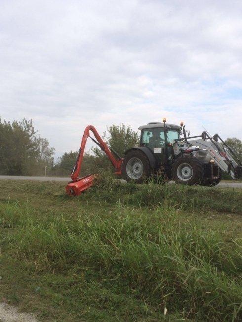 trattore durante taglio dell'erba sulla laterale di strada