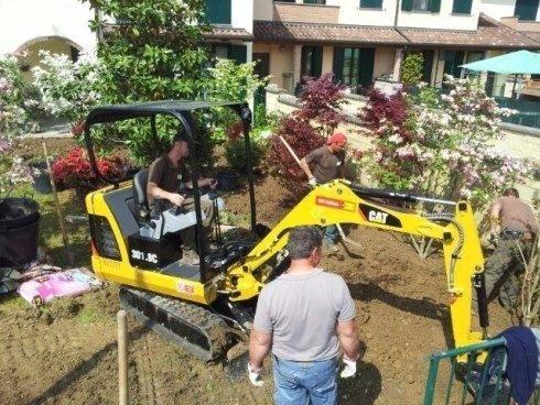 operai mentre lavorano in un giardino con scavatore