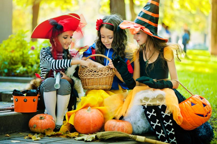3 YOUNG GIRLS IN COSTUMES FOR HALLOWEEN EATING CANDY TIPS TO PREVENT CAVITIES