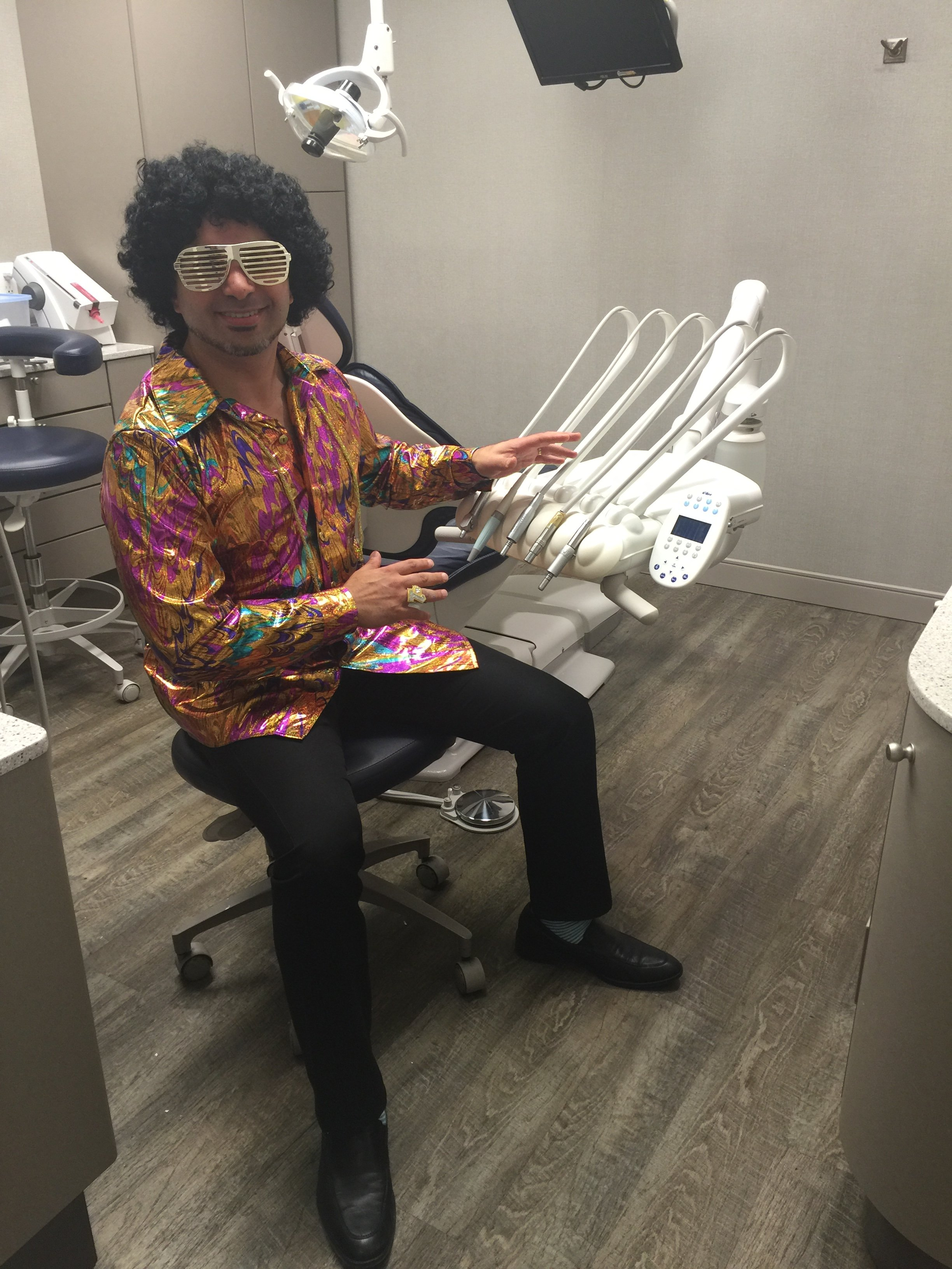 Dr Karim Lalani all dressed up in disco gear for Halloween at Clayton Heights Family Dental in Surrey.