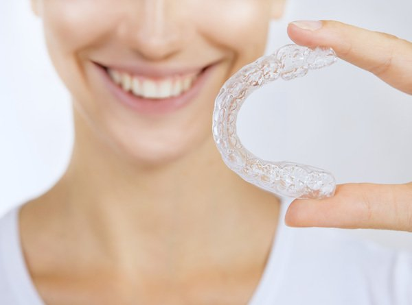 Woman showing her transparent Invisalign mold