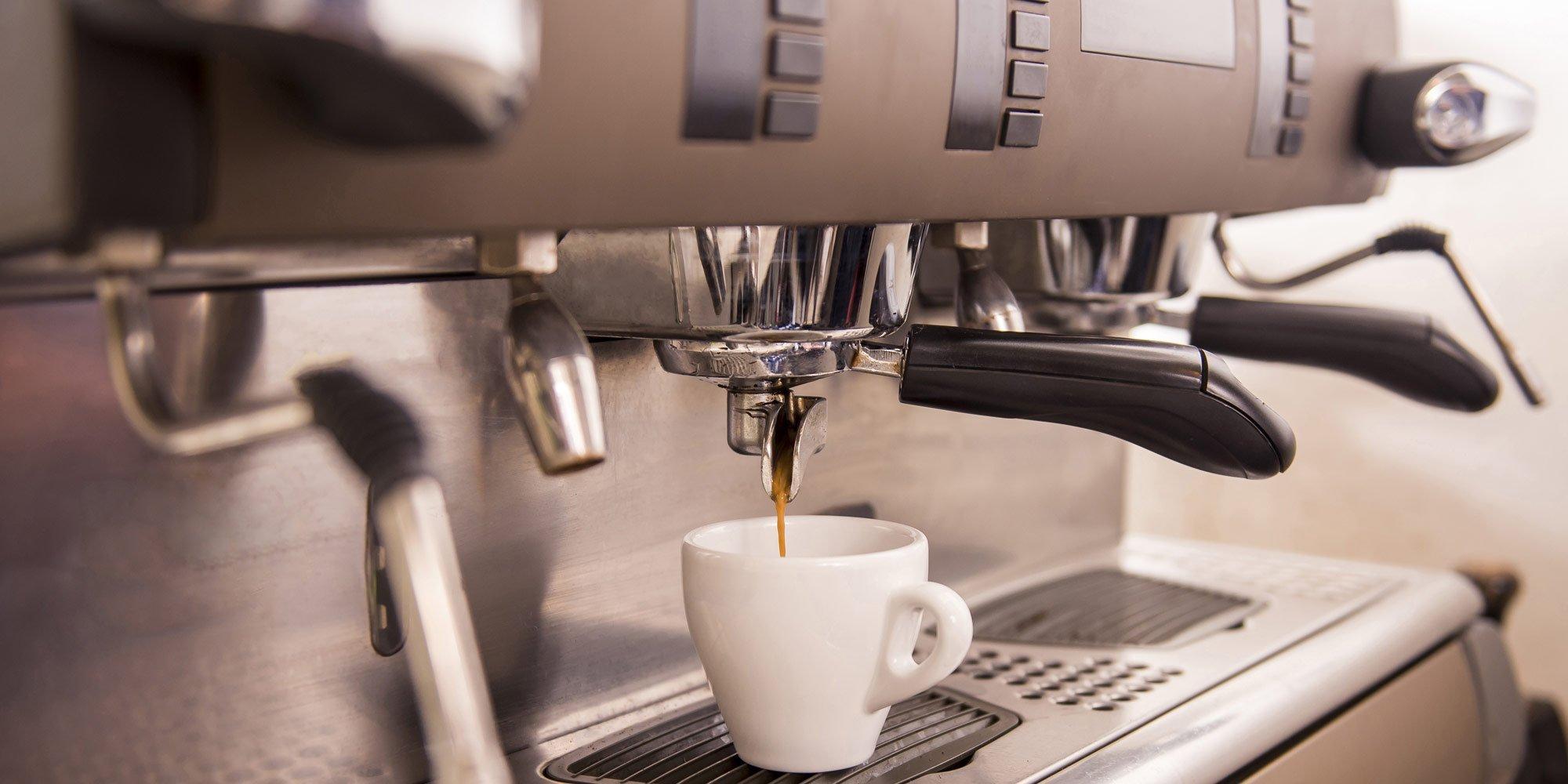 Il caffè sta sgorgando nella tazza dalla macchina da caffè ad Agrigento
