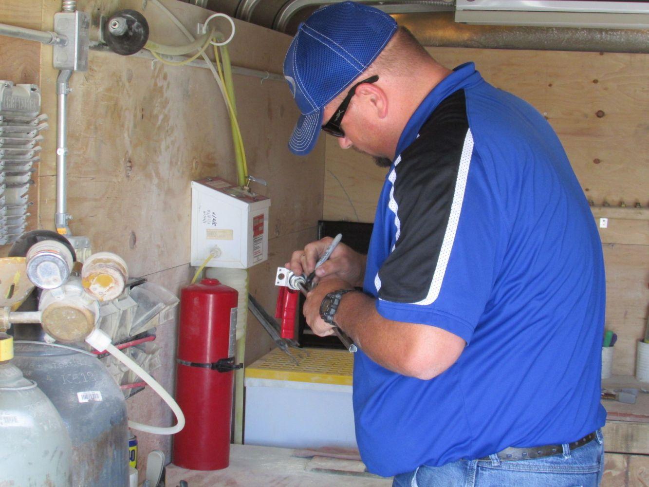 Man servicing a fire extinguisher.