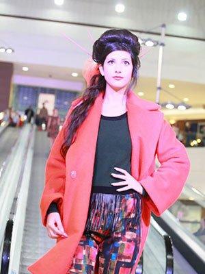 Pantaloni stampati, maglietta nera e cappotto rosso