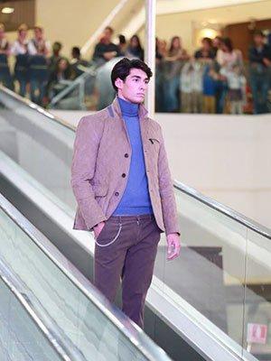 Giovane indossando pantalon marrone, jersey blu di collo alto e giacca marrone chiaro